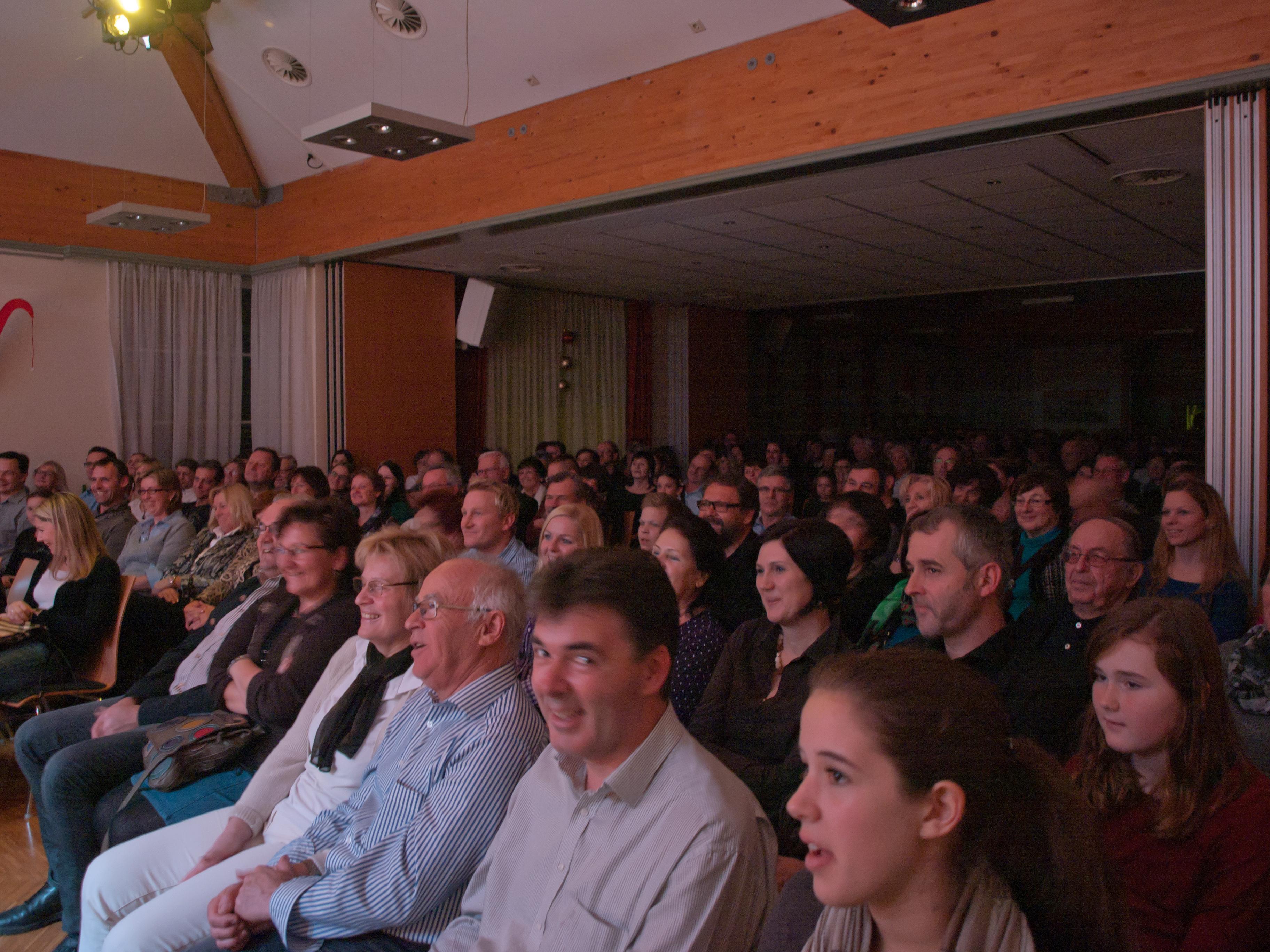 ein voller Saal mit lächelnden und glücklichen Besuchern in Adventstimmung